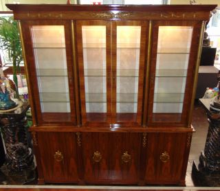 "Custom Madagascar Rosewood Sideboard Display Cabinet Custom Madagascar Rosewood Sideboard Display Cabinet. 4 Beveled Glass Doors with Glass Shelves and lights. 4 Door base with storage shelves. Measures 84"" (7 feet) tall x 75"" wide x 18"" deep. Condition is very good with minimal wear. No damage. Starting Bid $50. Auction Estimate $1200 - $1500."