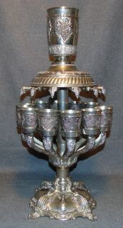 "Silver Plated Jerusalem Kiddush Cups Set Wine Fountain Silver Plated Jerusalem Kiddush Cups Set Wine Fountain. Measures 22"" tall x 11"" wide. Overall condition is good with minor wear typical from age. Starting Bid $50. Auction Estimate $180 - $250."