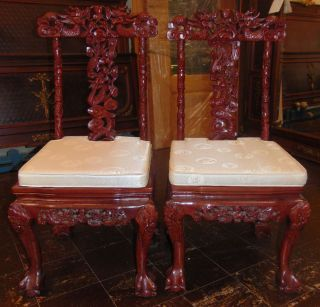 "Pair (2) of Oriental Carved Chairs Dragons & Koi Fish Pair (2) of Oriental Carved Chairs. Deep 3 Dimensional Figural Carving of Dragons & Koi Fish on both sides of chair back as well as legs and apron. Includes Silk like seat pads. Heavy Chairs. Each measures 41"" tall x 18"" wide. Condition is very good. No damage. Starting Bid $50 for both. Auction Estimate $80 - $120."