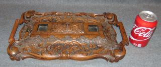 """Antique Carved Oak Double Inkwell Antique Carved Oak Double Inkwell or Inkstand. (No Glass ink well inserts present). Measures 17"""" wide x 10"""" deep x 2"""" tall. Overall condition is good with minor wear typical from age. Starting Bid $30. Auction Estimate $30 - $50."""