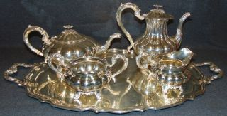 "Sterling Silver Birks Canada ""Mellon"" Tea & Coffee Set Magnificent 5 piece Sterling Silver Tea & Coffee Set by Henry Birks & Sons, Montreal 1943. The Melon pattern. Set includes Sterling Silver teapot, coffee pot, creamer, sugar bowl and Silver Plated Tray. With melon shaped bodies and acanthus capped scroll handles and spouts and shell feet.  Aprox 96 ounces of Sterling Silver not including tray. All pieces are marked properly. Condition is very good with minimal wear. No damage. No monograms. Starting Bid $50 for all. Auction Estimate $3000 - $4000."