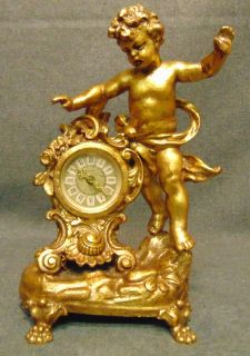 """Vintage Brass Cherub Clock by Mercede  Vintage German Brass Cherub Clock by Mercede. Wind-up mechanism. Measures 10-1/4"""" tall. Condition is good with some wear and scratches typical from age. No damage. Starting Bid $50. Auction Estimate $150 - $200."""