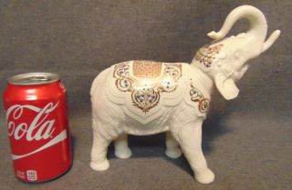 """Lenox China Jewels Palace Elephant Lenox China Jewels Palace Elephant. Crafted from fine ivory Lenox china, this elephant is very detailed with many bright colors, 24 karat gold, and enameled """"jewels"""". Measures 8-1/4"""" tall x 9"""" wide. Condition is very good. No Damage. Starting Bid $50. Auction Estimate $50 - $60."""