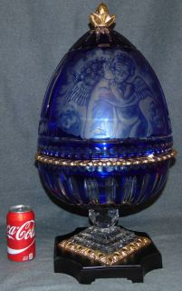 """Cobalt Cut & Etched Crystal Champagne Egg Beautiful Bohemian Style Cobalt Cut to Clear & Etched Crystal Champagne Egg With Ornate 24K Gold Gilded Bronze Rim and Base. Beautifully Etched with Cherubs on one side. Lid Opens to reveal 6 Champagne Flutes (not included). Also, can accommodate a Champagne Bottle and Ice. Measures 24"""" tall x 12-1/2"""" wide. Condition is New, Mint. No Damage. Starting Bid $50. Auction Estimate $1500 - $1800."""