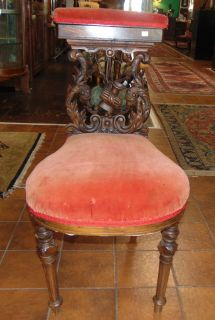 "Unusual Antique Carved Walnut Cock Fighting Chair  Unusual Antique Carved Walnut Cock Fighting or Smoking Chair with Red Velvet Upholstery. Circa 1880's. Heavily carved. Padded back rest opens up to reveal compartment. Stands 34"" tall x 18"" wide x 24"" deep. Condition is fair to good with some wear, scratches as well as a repair (see close-ups). Starting Bid $50. Auction Estimate $100 - $120."
