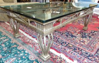 "Large Wrought Iron and Glass Coffee Table Large Wrought Iron and Glass Coffee Table. Very Heavy. Measures 21"" tall x 54"" wide x 38"" deep. Condition is excellent to very good with minimal wear. No damage. Starting Bid $50. Auction Estimate $250 - $350."