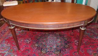 "Antique Mahogany Oval Dining Table Antique Mahogany Oval Dining Table with Bronze Banding and Accents. Circa 1940's. Measures 29"" tall x 62"" wide 43"" deep. Condition is good. 2 small marks on surface (see close-ups). Starting Bid $50. Auction Estimate $150 - $200."