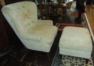 "Upholstered Armchair and Ottoman Upholstered Armchair and Ottoman. Chair measures 42"" tall x 40"" wide x 40"" deep. Condition is good with some minor wear and staining typical from age. Starting Bid $50. Auction Estimate $60 - $70."
