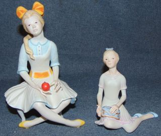 "2 Cybis Porcelain Figurines 2 Cybis Porcelain Figures of Seated Girls. One is Pollyanna, Girl Seated with Apple #465. She is 7-1/4"" tall. The other is Pandora. Retired. She is 4-3/4"" tall. Condition of both is very good. No Damage at all. Starting Bid $30 for both. Auction Estimate $30 - $50."