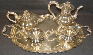 """Sterling Silver Birks Canada """"Mellon"""" Tea & Coffee Set  Magnificent 5 piece Sterling Silver Tea & Coffee Set by Henry Birks & Sons, Montreal 1943. The Melon pattern. Set includes Sterling Silver teapot, coffee pot, creamer, sugar bowl and Silver Plated Tray. With melon shaped bodies and acanthus capped scroll handles and spouts and shell feet. Aprox 96 ounces of Sterling Silver not including tray. All pieces are marked properly. Condition is very good with minimal wear. No damage. No monograms."""