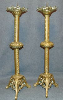 """Pair of Gothic Style Brass Candlesticks Pair of Gothic Style Brass Candlesticks. Possibly from a church. Each measures 23"""" tall. Condition is very good with minimal wear. No damage. Needs polish. Several Shipping Options Available. Starting Bid $100 for pair. Auction Estimate $120 - $200."""