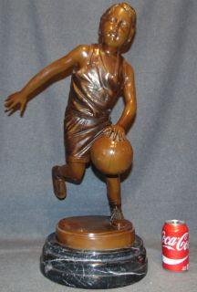 """Bronze Boy Basketball Player on Marble Bronze Boy Basketball Player Sculpture on a Black Marble Base. Artist Signed. Also, Foundry mark. Measures 25-1/2"""" tall x 11"""" wide. Condition is very good with minimal wear. No damage. This Sculpture is made entirely from Bronze with a Marble Base. Starting Bid $200. Auction Estimate $300 - $350."""