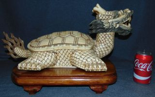 "Bone Feng Shui Dragon Turtle Sculpture Bone Feng Shui Dragon Turtle Sculpture on a Carved Wood Base. Measures 13"" tall x 23"" wide x 12"" deep. Overall condition is good with some losses and repairs (see photo close-ups). Several Shipping Options Available. Starting Bid $100. Auction Estimate $120 - $200."