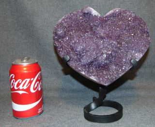 """Large Heart Shaped Amethyst Crystal Geode on Iron Stand Large Heart Shaped Amethyst Crystal Geode on Wrought Iron Stand. Brazilian. Measures 9-1/2"""" tall x 8-1/2"""" wide. Condition is very good. New condition. No Damage. Several Shipping Options Available. Starting Bid $200. Auction Estimate $220 - $250."""