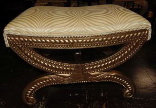 """Gold Upholstered Bench Ottoman Gold tone Upholstered Bench Ottoman. Measures 19"""" tall x 26"""" wide x 18"""" deep. Condition is very good with minimal wear. No damage. Several Shipping Options Available. Starting Bid $80. Auction Estimate $100 - $150."""