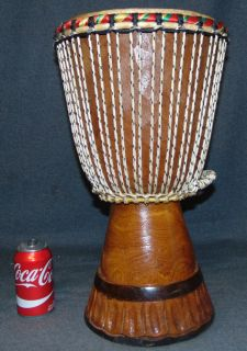 """African Djembe Drum African Djembe Drum. Authentic African Ceremonial Art. A djembe or jembe is a rope-tuned skin-covered goblet drum played with bare hands, originally from West Africa. Measures 19-1/2"""" tall x 12"""" wide. Overall condition is good. Wear consistent with age. Several Shipping Options Available. Starting Bid $50. Auction Estimate $80 - $150."""
