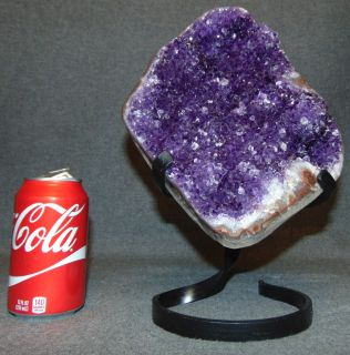 """Brazilian Amethyst Crystal Geode on Iron Stand Brazilian Amethyst Crystal Geode on Wrought Iron Stand. Measures 11-1/4"""" tall x 8"""" wide. Condition is very good. New condition. No Damage. Several Shipping Options Available. Starting Bid $50. Auction Estimate $200 - $300."""