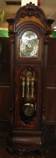 "Americana Capitol Grandfather Clock Americana Capitol Grandfather Clock. This Floor Clock has a plantation grown Indonesian SOLID MAHOGANY wood case. Dark brown aged finish is heavily distressed. Burl insets of birds eye maple are shown on 3 sides with full crown returns, and six pieces of beveled glass throughout including dial door, solid mahogany dial frame, hinged side access doors and full Bombe base. Carved feet and massive HAND carved mahogany crown accent the Grandfather sized 280mm dial with milled 1.5 mm brass Arabic numerals and raised antiqued cast corner element. The 270 mm twisted Lyre pendulum has a center raised cast design that accents the dial. Each of the bold large case carvings are of solid mahogany and done individually. The German made Triple chime movement plays a choice of 4/4 Westminster, Whittington or St Michael's Chimes with the traditional separate hour count, and automatic night silence feature included, plus a subsidiary seconds dial. Above the rotating blue moon phase dial are SOLID brass milled lunar numerals. Measures 92-1/2"" tall x 28"" wide x 14"" deep. Condition is very good with minimal wear. No damage. Several Shipping Options Available. Starting Bid $100. Auction Estimate $500 - $750."