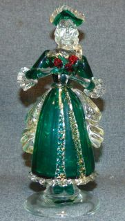 "24K Gold Murano Art Glass Woman Figure Vintage Venetian Murano Art Glass Woman Figure. Clear and Green Art Glass with Red Roses as well as 24K Yellow Gold Leaf Flecks. Measures 8-3/4"" tall. Condition is very good with minimal wear. No damage. Several Shipping Options Available. Starting Bid $30. Auction Estimate $80 - $100."