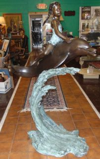 "Bronze Girl on Dolphin Fountain Sculpture Large Bronze Girl, Riding a Dolphin on a Big Wave Fountain Sculpture. High Quality Bronze with excellent Detail and patina. Cast and crafted one piece at a time in the traditional lost wax method. Bronze may be used indoor or outdoor. Sculpture functions as a fountain feature as well and is pre-Fitted to accept Water Pump for Fountain Feature. Measures 61"" tall x 46"" wide x 26"" deep. Condition is Brand New, Mint. No Damage at all. Several Shipping Options Available. Starting Bid $1,500. Auction Estimate $2,000 - $2,500."