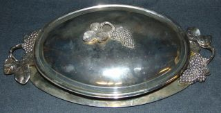 """Godinger 3 piece Silver Plated Casserole Godinger 3 piece Oval Silver Plated Grape & Leaf Casserole with Covered Lid, Handle Dish Tray and glass Casserole Dish. Measures 20"""" x 10"""". Condition is very good with some wear and minor surface scratches typical from age. No damage. Needs Polish. Marked """"Godinger Silver Art Co."""". Starting Bid $30. Auction Estimate $40 - $50."""