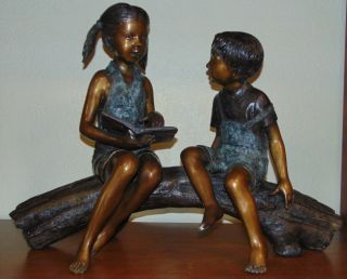 """Bronze Boy & Girl Reading a Book Sculpture Beautiful Bronze Boy & Girl Sculpture. Both sitting on a Log, Reading a Book. High Quality Bronze with excellent Detail and various shades of patina. Bronze may be used indoor or outdoor. Cast and crafted one piece at a time in the traditional lost wax method. Sculpture measures 26"""" tall x 32"""" wide x 16"""" deep. Condition is Like New. Very good. No Damage. Several Shipping Options Available. This Sculpture is made entirely from Bronze. Starting Bid $1,000. Auction Estimate $1,250 - $1,600."""