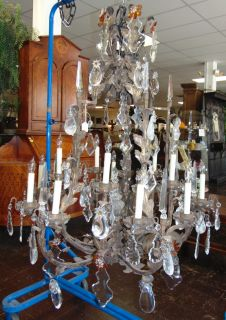 """Large 15 Light Iron & Crystal Chandelier Large 15 Light Iron & Crystal Chandelier. Measures 54"""" tall x 40"""" wide. Condition is good. Several Shipping Options Available. Starting Bid $400. Auction Estimate $500 - $600."""