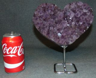 """Heart shaped Amethyst Geode on a Stand Heart shaped Amethyst Geode on an Iron Stand. Geode Measures 5-1/2"""" tall x 8"""" wide. Total height on stand is 9"""". Condition is Like New. Very good. No Damage. Several Shipping Options Available. Starting Bid $150. Auction Estimate $180 - $250."""