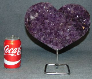 "Heart shaped Amethyst Geode on a Stand Heart shaped Amethyst Geode on an Iron Stand. Geode Measures 7"" tall x 10"" wide. Total height on stand is 10-1/2"". Condition is Like New. Very good. No Damage. Several Shipping Options Available. Starting Bid $200. Auction Estimate $250 - $350."
