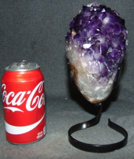 """Large Amethyst Crystal Geode on Iron Stand  Beautiful & Large Brazilian Amethyst Crystal Geode on a Wrought Iron Stand. These are spectacular, one-of-a-kind specimens from Brazil. Measures 9"""" tall x 4"""" wide x 7"""" deep. Condition is very good. New condition. No Damage. Several Shipping Options Available. Starting Bid $100. Auction Estimate $120 - $150."""