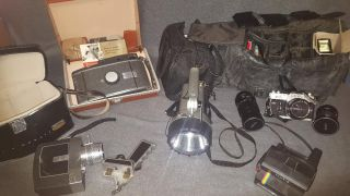 Misc Lot Cameras & Rechargable Flashlight Misc Lot of Cameras & a Rechargable Flashlight. Includes: Canon 35mm Camera plus accessories, Bell & Howell Directors Series Video Camera and a Poloroid Camera. Shipping Options Available. Starting Bid $80. Auction Estimate $80 - $200.