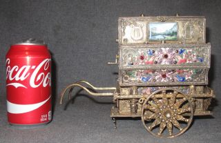 """Vintage Jeweled Hurdy Gurdy Musical Piano Magnificent, Vintage Jeweled Hurdy Gurdy Musical Piano Cart on 2 Wheels. Engraved, Enameled and Highly Decorated with Emeralds, Pearls and Garnets. Measures 7"""" tall x 9"""" wide x 4"""" deep. Overall condition is very good. Musical mechanism not working condition. Starting Bid $2,500. Auction Estimate $2,500 - $5,000."""