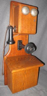 """Antique Oak Wall Phone Antique Oak Wall Phone. Measures 31"""" tall x 11-1/2"""" wide x 9"""" deep. Overall condition is good to fair. Wear consistent with age and use. Starting Bid $100. Auction Estimate $100 - $200."""