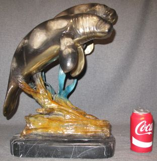 "Bronze Manatees Sculpture on Marble Bronze Manatees Sculpture on a Marble Base. Artist Signed. Measures 19"" tall x 13"" wide x 14"" deep. Condition is Brand New, Mint. No Damage at all. Starting Bid $500. Auction Estimate $500 - $800."