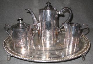 """English Barker Ellis Silver Tea Set with Sheffield Tray English Silver Plated 3 piece Tea Set by """"Barker Ellis"""". Includes Tea Pot ( 6-1/2"""" tall), Creamer ( 4-1/2"""" tall) and Sugar ( 3-1/4"""" tall). Also includes Silver Plated Footed Tray marked """"James Dikon & Sons - Sheffield"""". Condition of all is good. No damage. Starting Bid $80. Auction Estimate $150 - $450."""