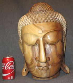 """Carved Wood Buddha Head Carved Wood Buddha Head. Measures 16-1/2"""" tall x 10-1/2"""" wide x 10-1/2"""" deep. Condition is good. Few separations in wood. No damage. Starting Bid $80. Auction Estimate $150 - $250."""