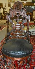 "Antique Carved Walnut Slipper Chair Antique Carved Walnut Slipper Chair. Circa 1870. Measures 41"" tall. Condition is good with some wear and scratches typical from age. Also, Finial is broken off on one side. Starting bid $100. Auction Estimate $200 - $400."
