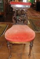 "Unusual Antique Carved Walnut Smoking Chair  Unusual Antique Carved Walnut Smoking Chair with Red Velvet Upholstery. Circa 1880's. Heavily carved. Padded back rest opens up to reveal compartment. Stands 34"" tall x 18"" wide x 24"" deep. Condition is fair to good with some wear, scratches as well as a repair (see close-ups). Starting Bid $200. Auction Estimate $300 - $500."