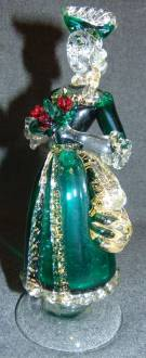 "Murano Art Glass Woman Figure 24K Gold Vintage Venetian Murano Art Glass Woman Figure. Clear and Green Art Glass with Red Roses as well as 24K Yellow Gold Leaf Flecks. Measures 8-3/4"" tall. Condition is very good with minimal wear. No damage. Several Shipping Options Available. Starting Bid $100. Auction Estimate $120 - $150."